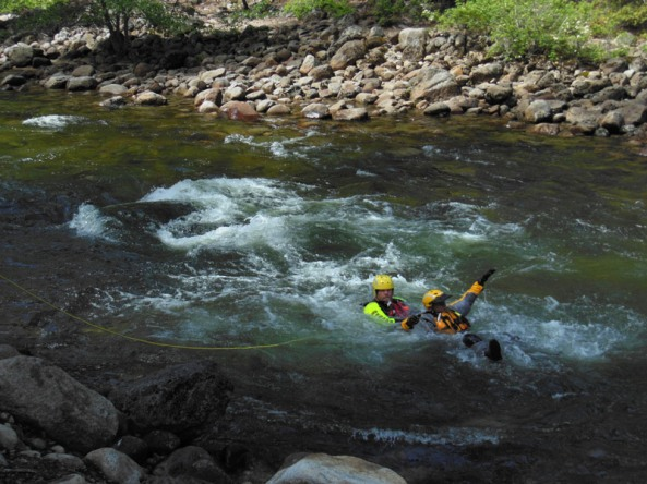 Here rescuers demonstrate one technique where the rescuer has a safety line to the shore and swims out to the victim. Notice here that both people are in the right position for running rapids, with their feet downstream to protect them from rocks.