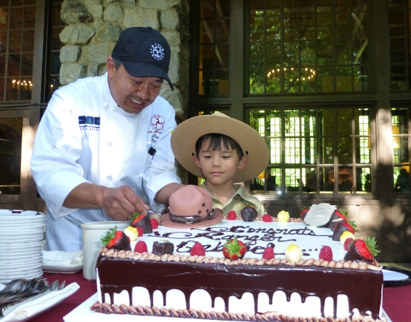 Chef Paul Padua helps Ranger Gabriel cut the cake at The Ahwahnee. Photo by Michelle Hansen.