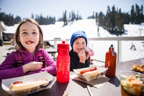 Enjoying sunshine and a snack on the deck at Badger Pass.